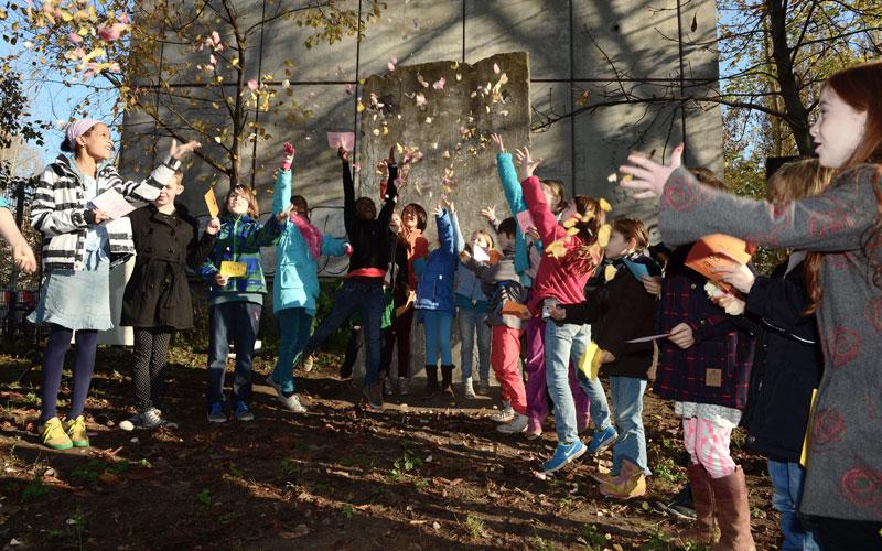 Kinder springen hoch und werfen Laub