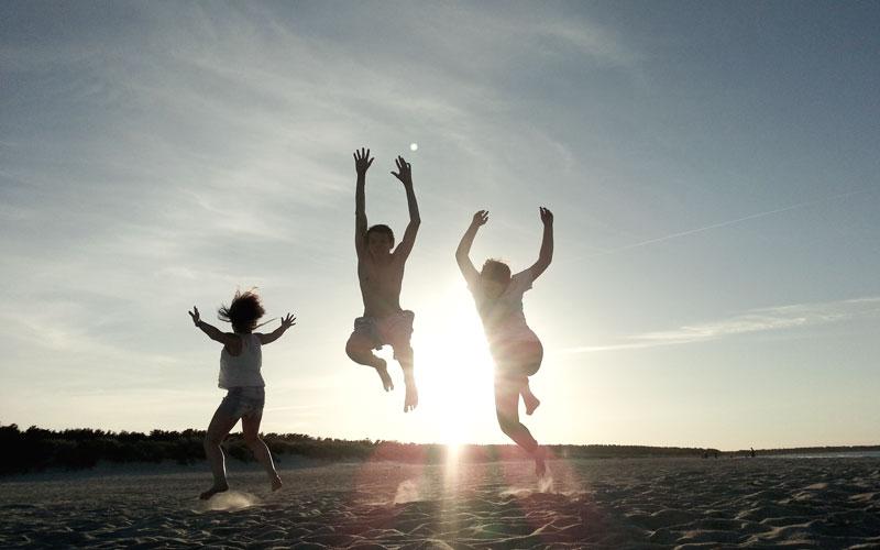 Kinder springen hoch im Sand und die Sonne geht unter