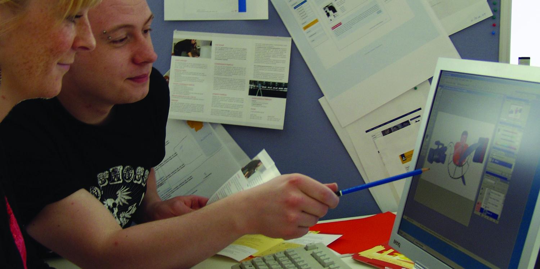 Zwei Personen schauen auf einem Bildschirm und die eine Person zeigt mit einem Bleistift auf etwas vom Bildschirm