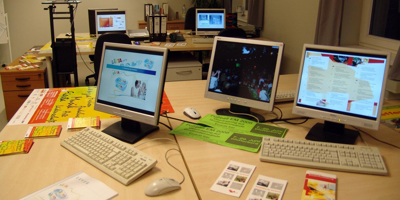 Mehrere Tische mit mehreren Bildschirmen, Tastaturen und Mäusen