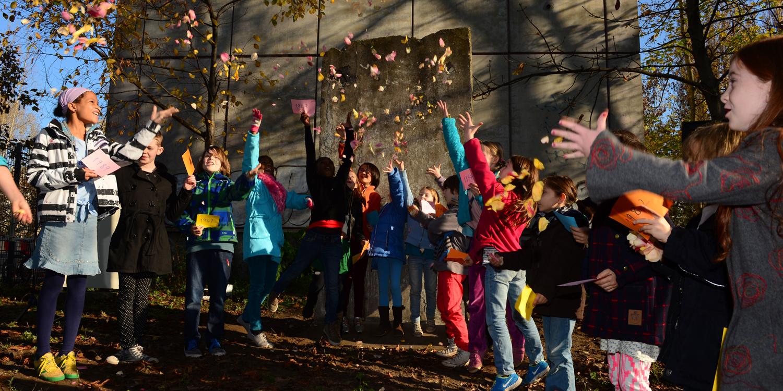 Mehrere Schüler werfen Blätter in die Luft