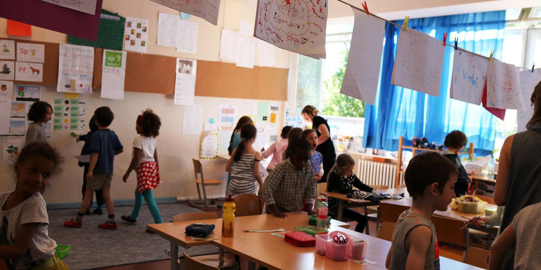 Ein Klassenraum mit mehreren Schülern und einer Lehrerin, in dem Raum hängt eine Wäscheleine mit mehreren Plakaten