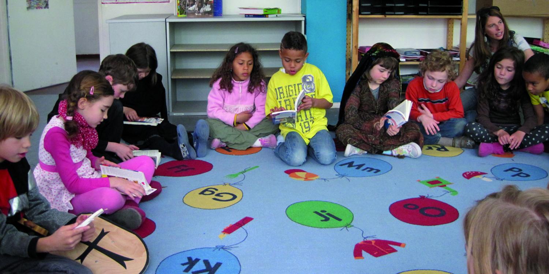 Schüler lesen gemeinsam ein Buch in einem Raum.