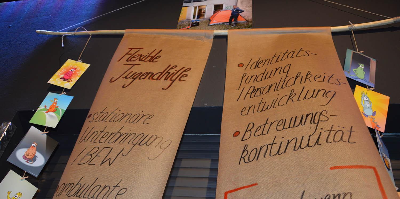 Auf zwei großen herunterhängenden Papierbahnen steht geschrieben, was die Flexible Jugendhilfe beinhaltet, wie z.B. Beratung