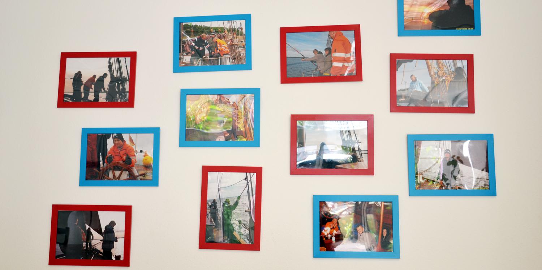 Mehrere Fotos an einer Wand, die Personen auf einem Schiff zeigen