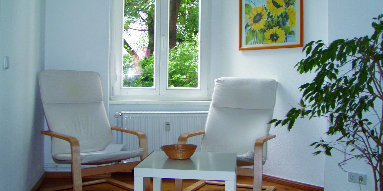 Zwei Stühle mit einem Tisch und einem Fenster