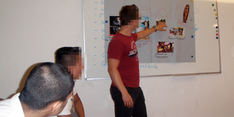 drei männliche Personen schauen auf ein Plakat über Gewalt, eine der Personen erklärt etwas auf dem Plakat