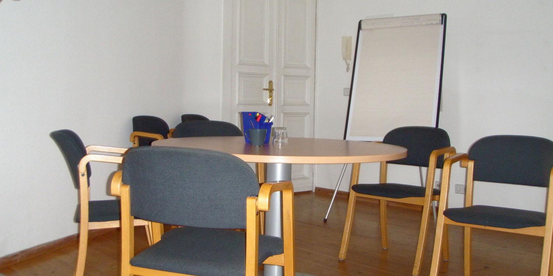 Ein Tisch mit mehreren Stühlen dran und einem großen Schreibblock
