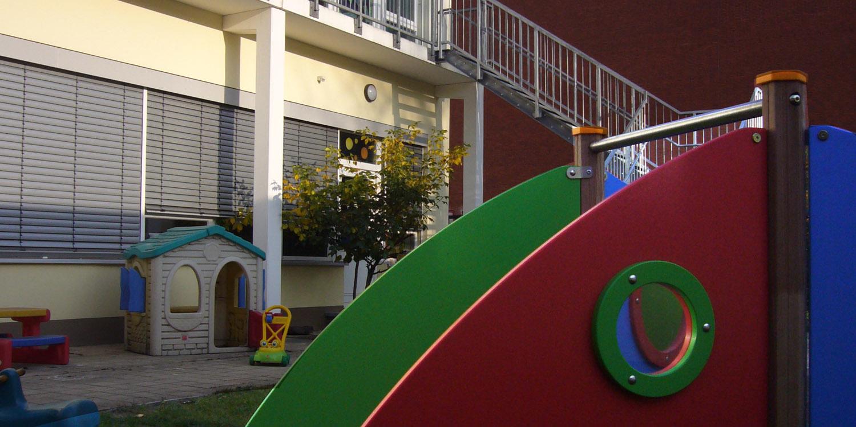 Kleiner Teil des Außenbereichs mit Spielhaus und einem Klettergerüst und Hausfassade der Kita