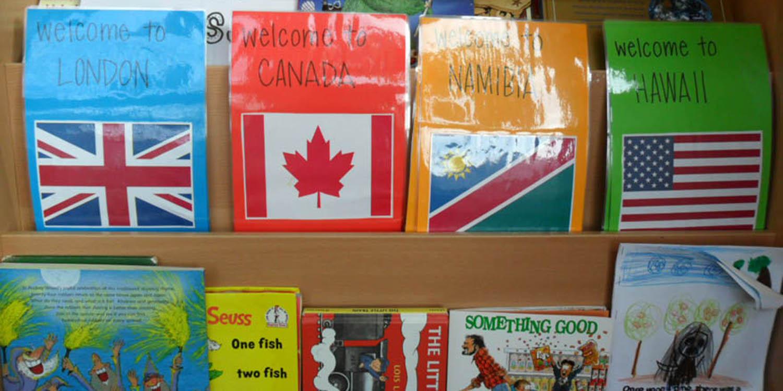 Regal mit mehreren Büchern und vier Flyern. Auf den vier Flyern wird jeweils eine Länderflagge und 'willkommen in' dem jeweiligen Land dargestellt
