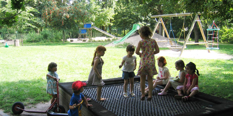 Mehrere Kinder, die bei einem Spielplatz auf einem Trampolin hüpfen