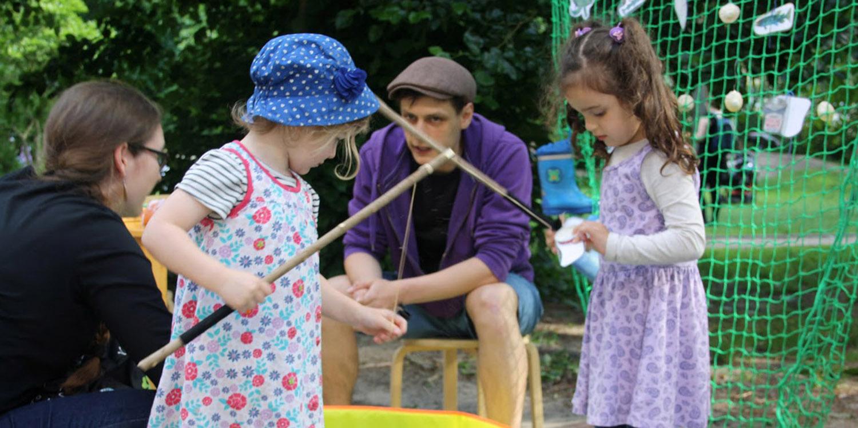 Zwei Kinder, die mit einer selbstgebauten Magnetangel spielen und von zwei Erziehern beaufsichtigt werden.
