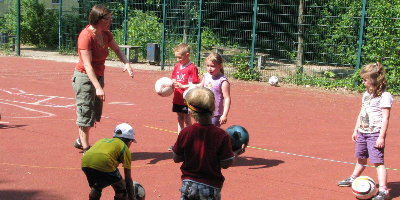 Auf einem Sportplatz erklärt eine Erzieherin mehreren Kindern mit Fußbällen etwas.