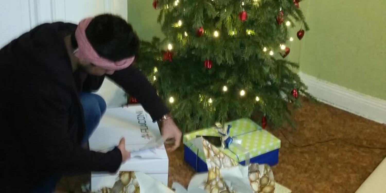 Eine Person hockt vor einem Weihnachtsbaum mit Geschenken