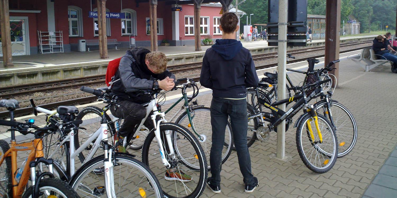 Zwei Personen stehen an einem Bahnhof, auf dem mehrere Fahrräder stehen