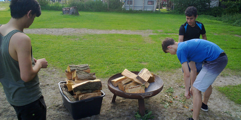 Drei Personen stehen um eine Metallschale, in der Schale sind mehrere Holzscheiten und daneben steht auch noch eine Kiste mit Holzscheiten