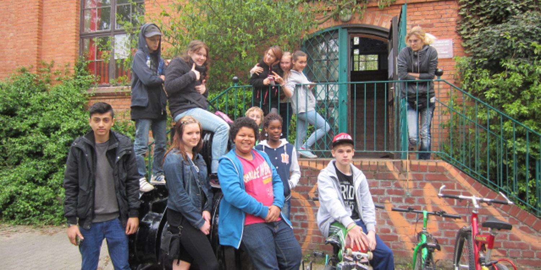 Mehrere Jugendliche sitzen und stehen vor einem Gebäude