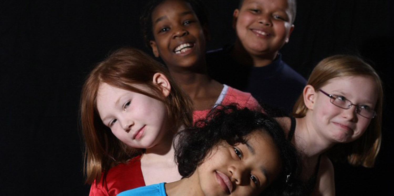 Fünf Jugendliche aus verschiedenen Kulturkreisen nebeneinander und lachen