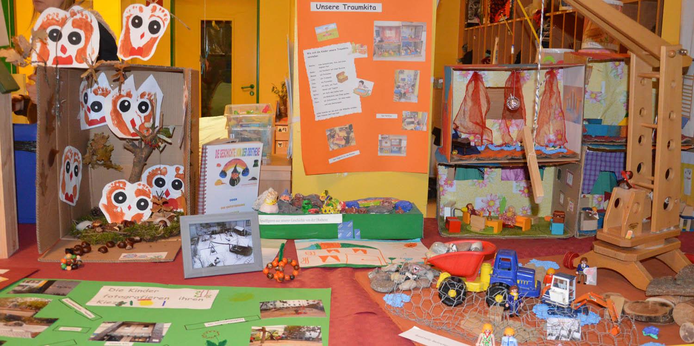 Tisch mit Spielzeug, selbstgebastelte Sachen und Fotos von der Gegend der Kita