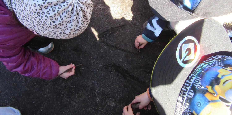 Mehrere Kinder, die draußen mit Stöckern in die Erde etwas zeichnen