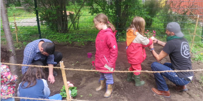 Zwei Erwachsene und vier Kinder pflanzen Blumen an