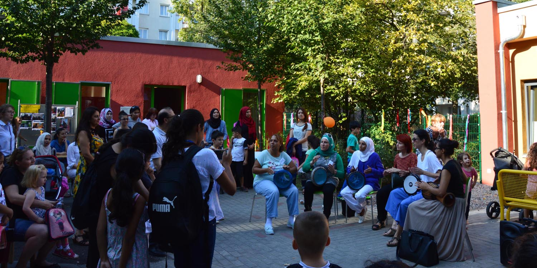In der Mitte spielt eine Band mit einer Flöte und mehreren Trommeln und ringsherum stehen Erwachsene und Kinder