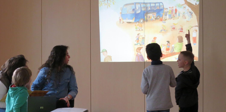 Fünf Personen schauen sich ein an die Wand projiziertes Bild an