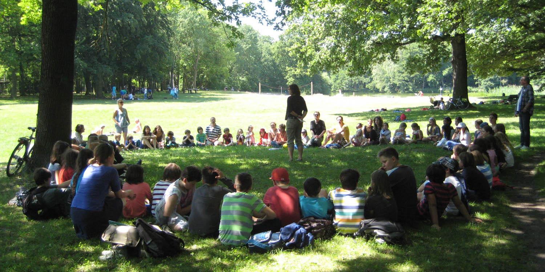 Schüler und Lehrer sitzen auf einer Wiese in einem großen Kreis und in der Mitte steht eine Lehrerin