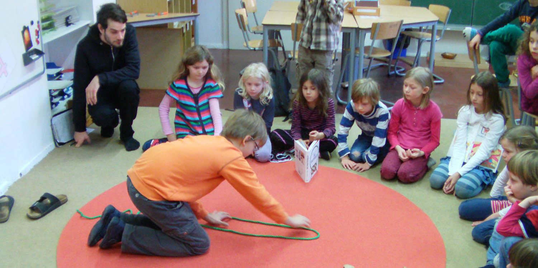 Schüler sitzen in einem Halbkreis und in der Mitte kniet ein Junge der ein Seil in der Hand hat.