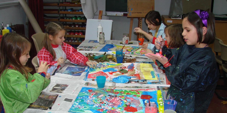Mehrere Schülerinnen, die ein Bild malen.