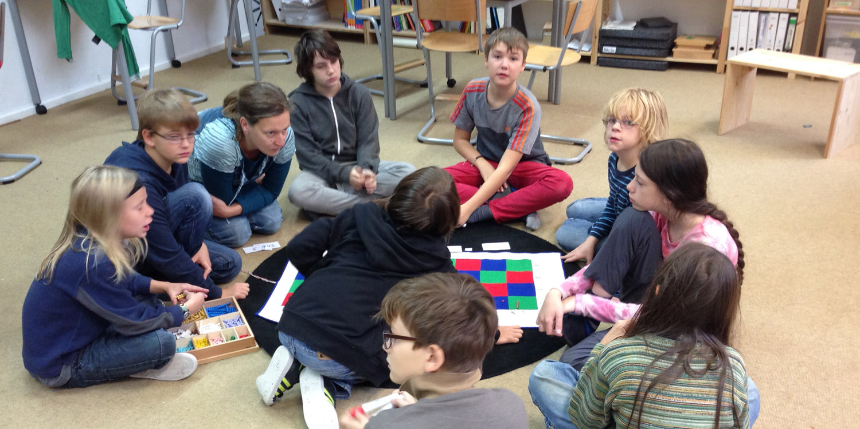 Mehrere Schülerund Schülerinnen sitzen in einem Kreis und machen eine Gruppenaufgabe miter Kugeln und Quadraten.
