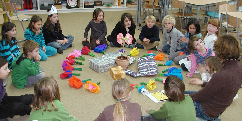 Eine Klasse sitzt in einem Kreis und in diesem Kreis befinden sich selbstgebastelte Blumen, eine echte Blume und fünf Geschenke