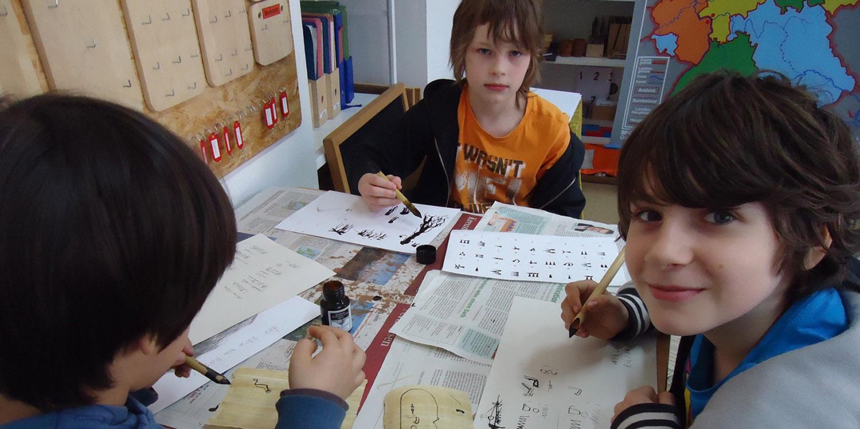 Drei Schüler, die mit Tinte Symbole zeichnen.