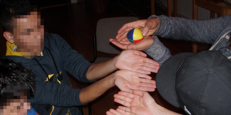 Jugendliche versuchen, gemeinsam einen Ball ihre aneinandergereihten Händer herabrollen zu lassen, ohne, dass er herunterfällt.