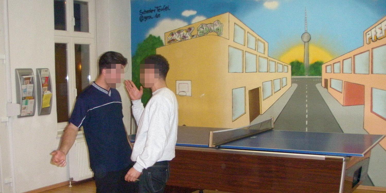 Zwei junge Männer stehen sich in einer bedrohlichen Haltung gegenüber und streiten.