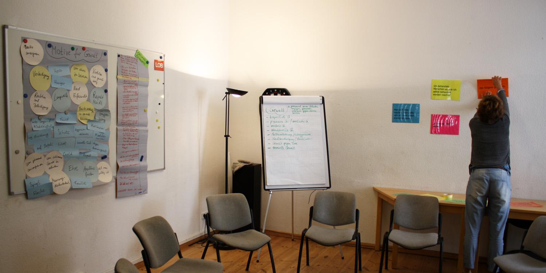 Es stehen mehrere Stühle im Kreis aufgestellt und im Hintergrund sieht man einen Frau, die einen Zettel aufhängt, außerdem sieht man mehrere Plakate zu Gewalt