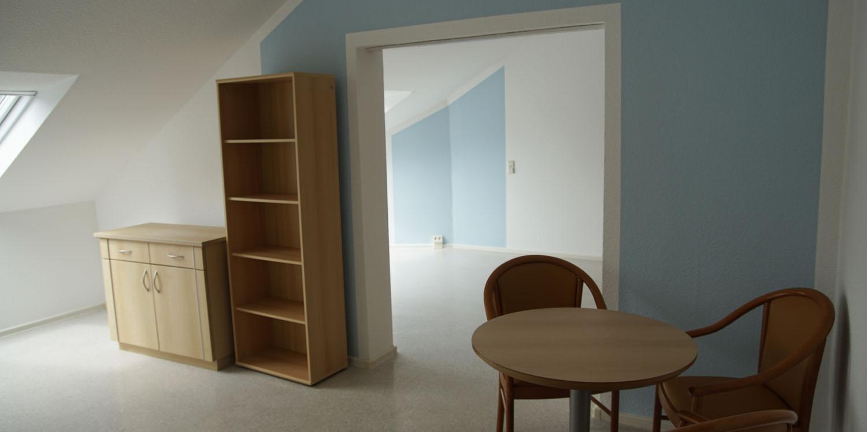 Ein Raum mit einem großen und einem kleinen Schrank und einem Tisch mit zwei Stühlen. Da der Türrahmen keine Tür hat sieht man noch einen zweiten Raum mit einer blauen Wand