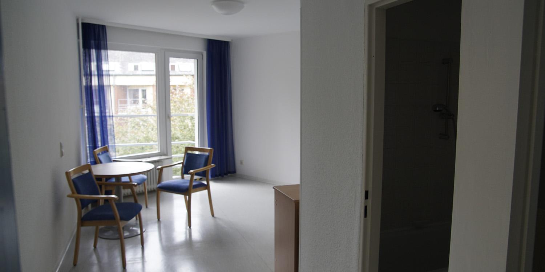 Ein Raum, der mit einem Tisch mit zwei Stühlen und einem kleinen Schrank gefühlt ist. Im Hitnergrund sieht man ein Fenster und eine Tür zum Balkon