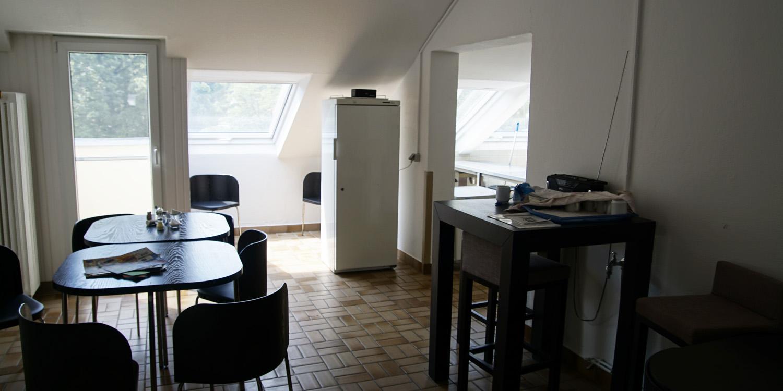 Der Raum hat mehrere Tische und Stühle und besitzt einen Kühlschrank. Außerdem besitzt der Raum mehrere Fenster und eine Dachschräge