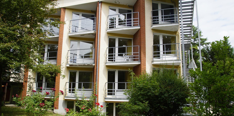 Eine grontale Häuserfront mit einem grünen Garten davor