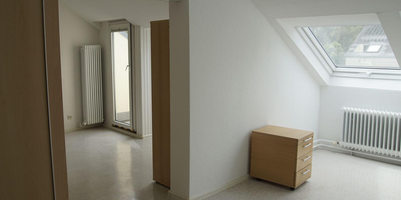 Zwei Räume mit einer Dachschräge. In einem Raum ist ein kleiner Schrank und in dem anderen ist ein großer Schrank