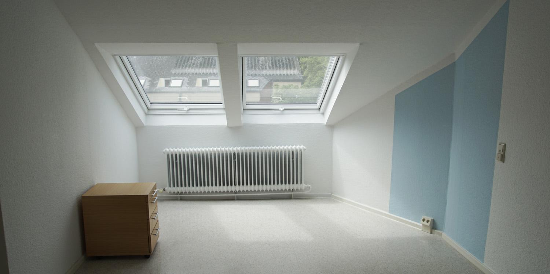 Ein Raum mit einer Dachschräge und zwei Fenstern. Der Raum hat eine blaue Wand und einen kleinen Schrank