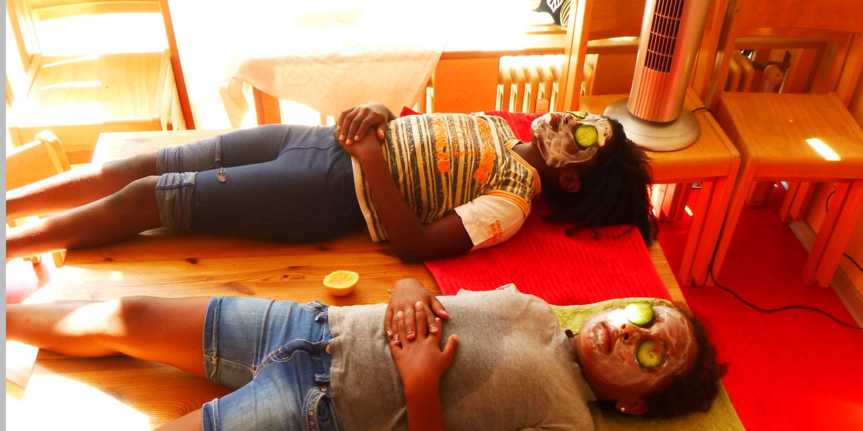 Zwei Kinder, die liegen und eine Creme im Gesicht haben und Gurkenscheiben liegen auf den Augen von den beiden Kindern