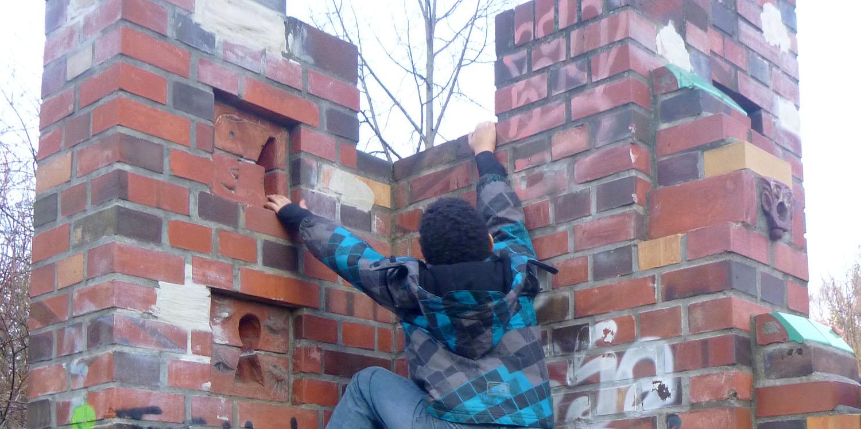 Ein Junge klettert eine Mauer hoch