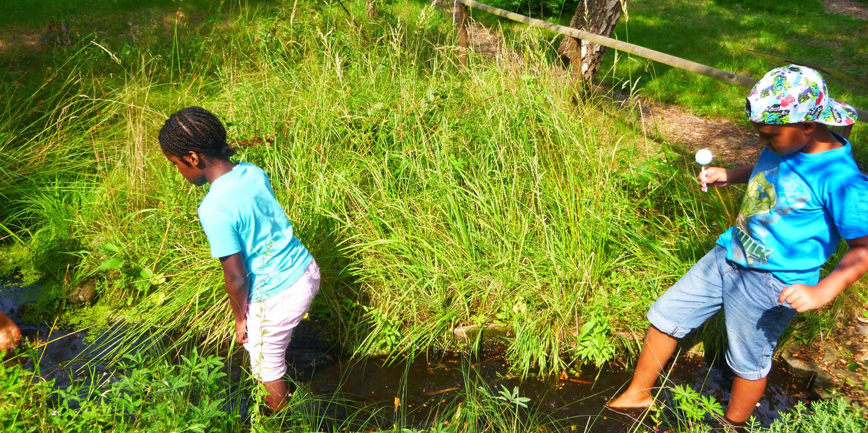 Zwei Kinder stehen mit den Füßen in einem kleinen Gewässer