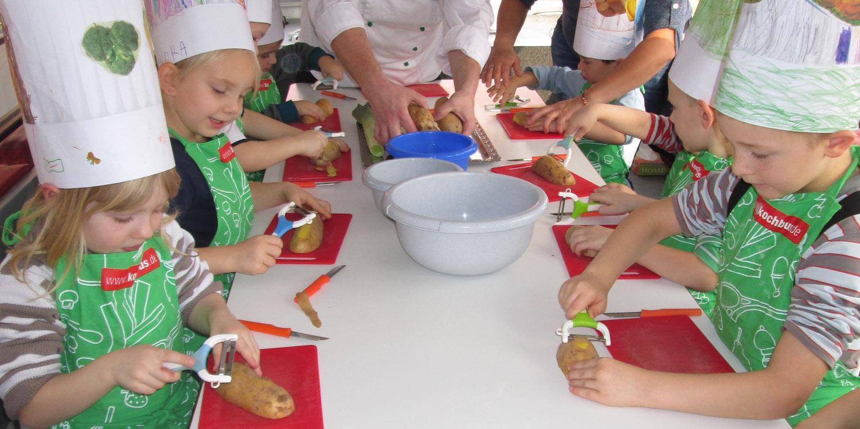 Mehrere Kinder, die Kartoffeln schälen unter Aufsicht