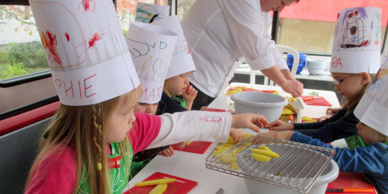 Kinder packen geschnittene Kartoffeln auf ein Blech.