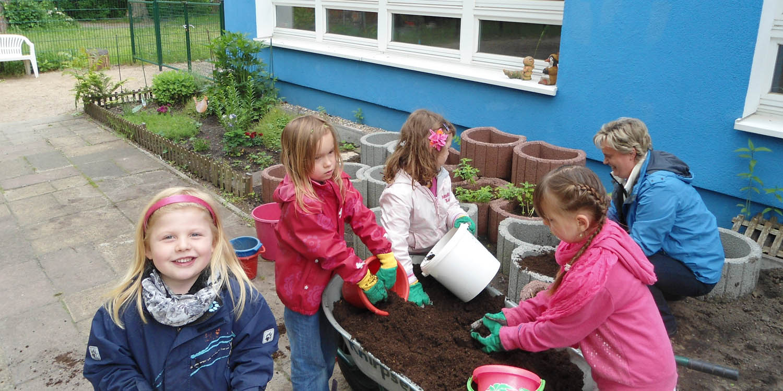 Mehrere Kinder und eine Erzieherin, die Erde aus einer Schubkarre in Eimer umfüllen. Im Hintergund sieht man mit Erde befüllt und unbefüllte Blumenkästen.