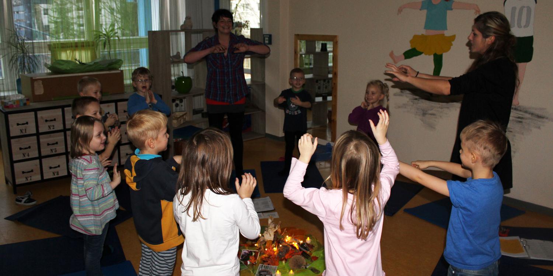 Mehrere Kinder und Erzieher stehen in einem Kreis und machen Bewegungen