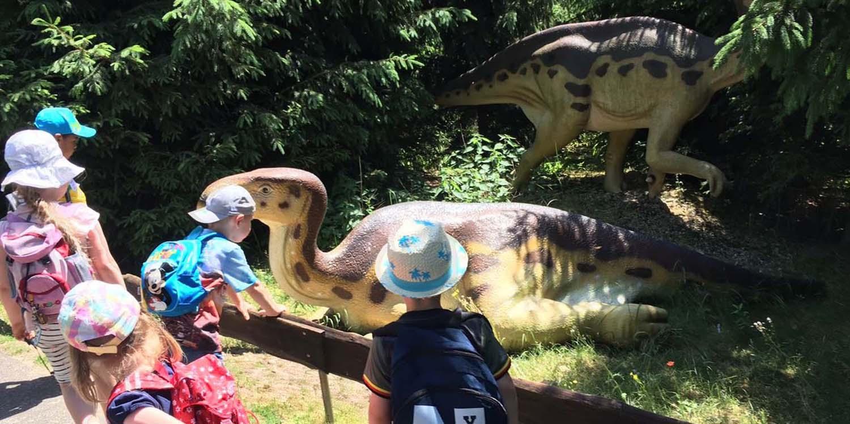 Einige Kinder bestaunen dargestellte Dinosaurier